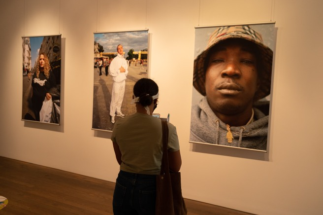 A Visitor Looking at Nous Sommes Halles by Mohamed Bourouissa at the Photographers' Gallery
